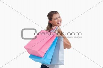 Back view of a cheerful woman holding shopping bags