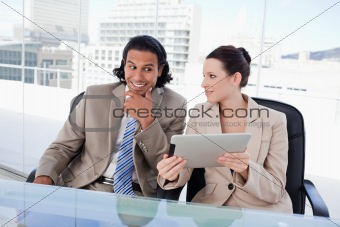 Smiling business team using a tablet computer