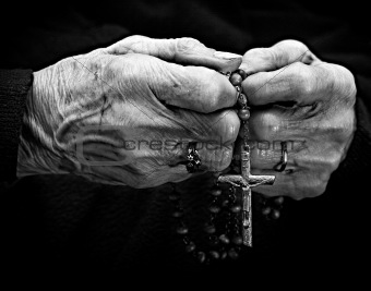 Old woman hands with a rosary