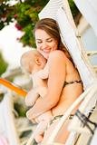 Happy young mother laying on sunbed and hugging baby