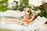 Young mother laying on sunbed and playing with baby