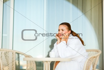 Beautiful woman in bathrobe sitting at table on terrace and dreaming
