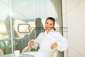 Portrait of beautiful smiling woman in bathrobe sitting at table on terrace