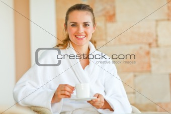 Beautiful woman in bathrobe sitting at table on terrace and having coffee