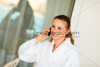 Smiling beautiful female in bathrobe sitting at table on terrace and speaking mobile