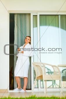 Beautiful woman in bathrobe standing on terrace near big windows and having cup of coffee