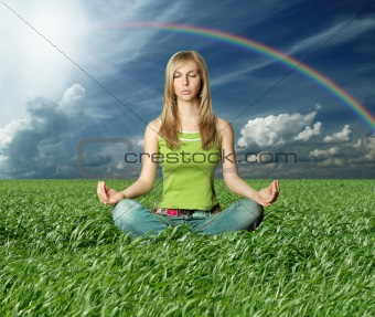 Blonde in lotus pose in green grass