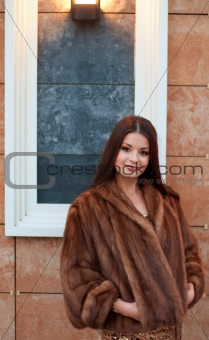 Portrait of luxurious young woman in a fur coat