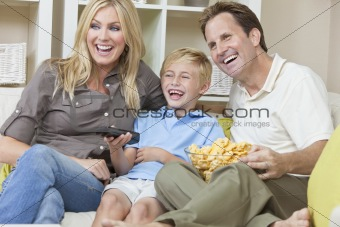 Happy Family Sitting on Sofa Laughing Watching Television