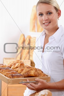 Young female baker with croissants and pain au chocolats