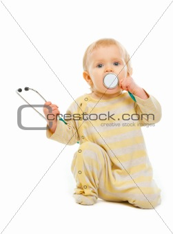 Baby playing stethoscope isolated on white