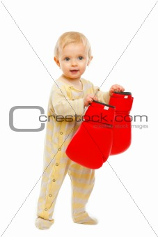 Adorable baby standing with boxing gloves isolated on white