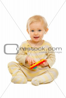 Adorable baby sitting on floor and playing with rattle isolated on white