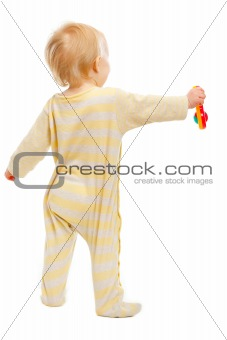 Baby standing with rattle back to camera isolated on white