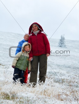 Family on autumn  mountain plateau with first winter snow
