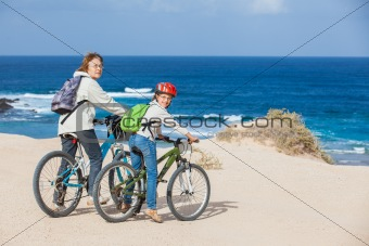girl and her grandmother on bikes on the beach