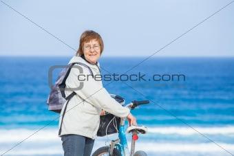 A nice senior lady riding a bike on the beach.