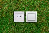 green energy concept: electric outlet and light switch on a grass