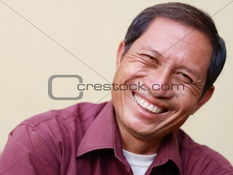 Happy mature Asian man smiling and looking at camera