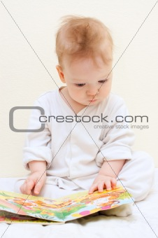 One year baby boy reads children's book
