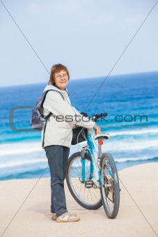 A nice senior lady riding a bike on the beach.