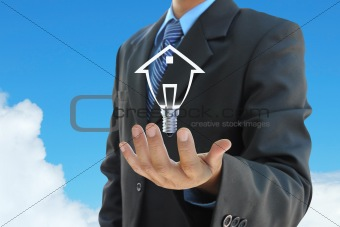 businessman hand holding a light bulb model of a house on sky