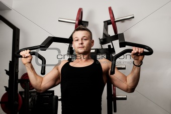 Man doing fitness training on machine with weights in a gym