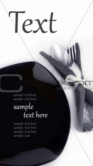 black plate with a fork and a spoon in a napkin