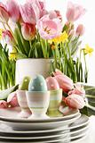 Easter eggs in cups with spring flowers on white