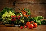Freshly picked vegetables in basket in wooden table