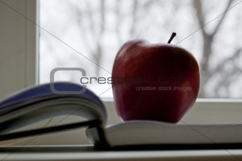 Apple lay on book next to window
