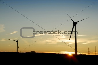 Silhouette of Two Wind Turbines at Dawn. UK