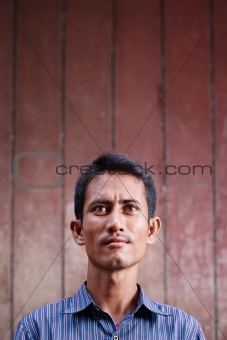 Portrait of mid adult asian man looking up