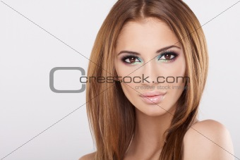 Portrait of beautiful woman with brown hairan with hands on face