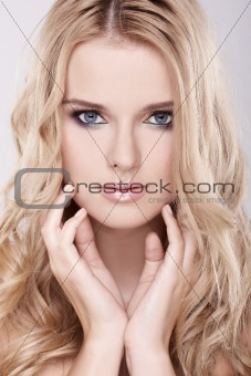 Closeup portrait of a beautiful young blond woman with hands on face