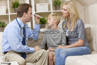 Male Doctor Home Visit Examining Boy Child With Mother