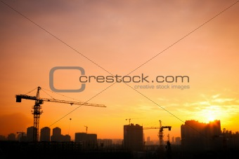 Silhouette of the tower crane on the construction site.