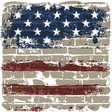 The American flag against a brick wall.