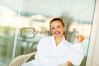 Portrait of smiling woman in bathrobe sitting on terrace