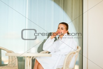 Thoughtful woman in bathrobe sitting at table on terrace
