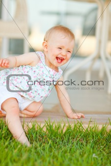 Smiling baby touching grass with leg