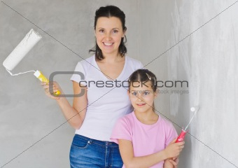 Happy Mother and douther painting a wall