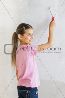 Happy girl painting a wall