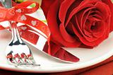 Red rose and cutlery on white plate