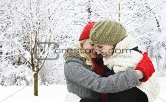 Two girl friends hugging outside in winter
