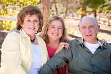 Portrait of Senior Couple with Daughter in the Park.