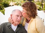 Happy Senior Couple Kissing in the Park.