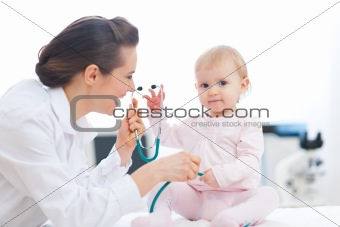 Pediatrician doctor playing with baby on examination