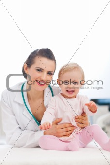 Portrait of happy pediatric doctor and baby