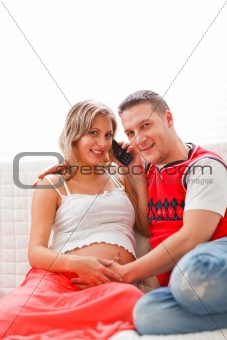 Happy pregnant woman with husband speaking mobile phone